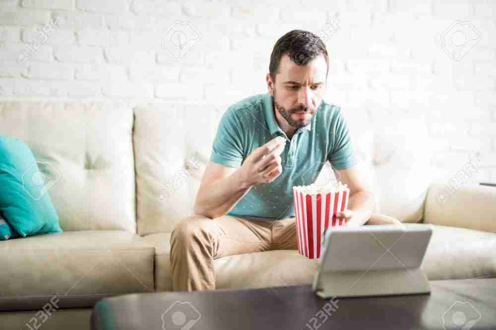 85486541-relaxed-man-watching-a-movie-in-a-tablet-computer-and-eating-some-popcorn.jpg